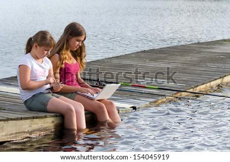 Girls choose social media instead fishing - stock photo