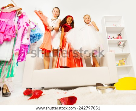 Girls choosing dresses while standing on sofa - stock photo
