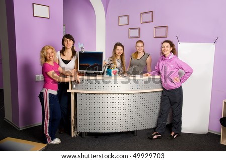 Girls - coach standing near the reception before the opening of the fitness center - stock photo