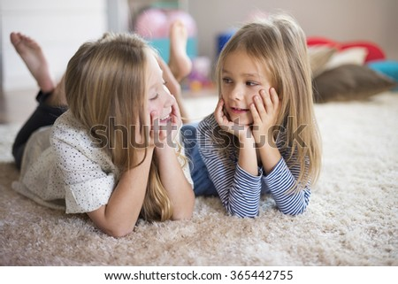Girls creating new ideas on the fluffy rug  - stock photo