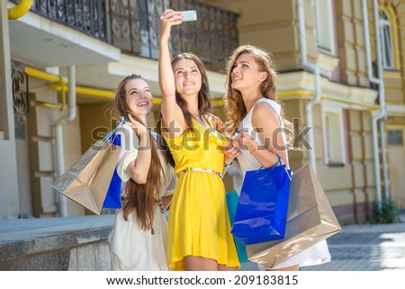 Girls doing selfie. Girls holding shopping bags and walk around the shops. Smiling girl photographed on a cell phone. Girlfriends having fun together - stock photo