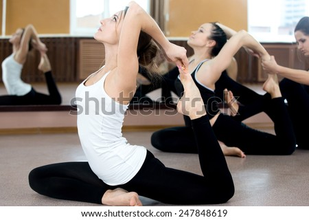 Girls doing yoga exercises in class, sitting in asana eka pada radzhakapotasana (One-Legged King Pigeon Pose) - hands grasps feet, instructor on the background coaching one of the yoga students - stock photo