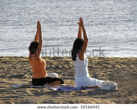 girls doing yoga on seacoast - stock photo