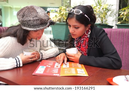 Girls drinking coffee in a cafeteria and looking at the menu to order more. - stock photo