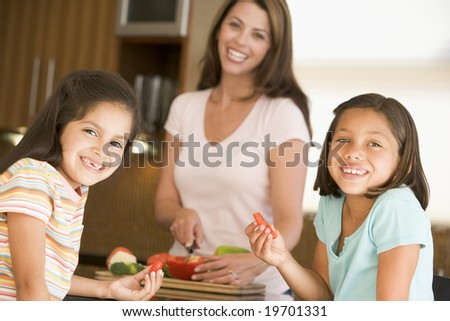Girls Eating Pepper Strips While Mother Is Preparing meal,mealtime