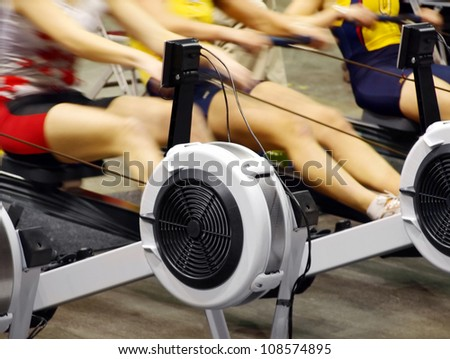 Girls  exercising in the gym on rowing machines - stock photo