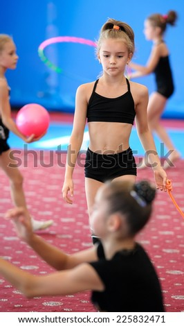 Girls exercising with ball and hula hoop during gymnastics class. Focus on the girl holding rope - stock photo