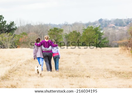 Girls Family Hugging Walking Outdoors Mother with teenage girls walking hugging in nature countryside landscape - stock photo