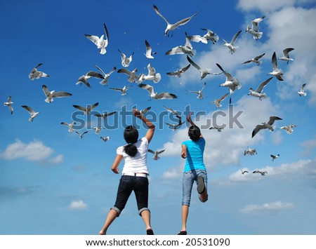 Girls feeding a flock of birds (seagulls) flying in the air - stock photo