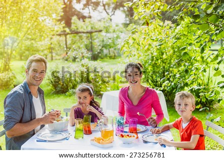 Girls first ! A grey hair father is serving melon to his daughter for a nice family lunch in the garden. - stock photo