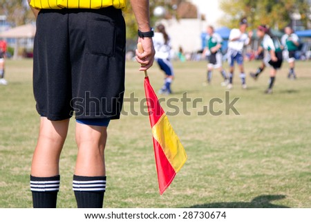 Girls' football soccer referee watching over a game - stock photo