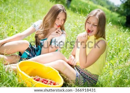 Girls gathering strawberry on bright summer day green  - stock photo