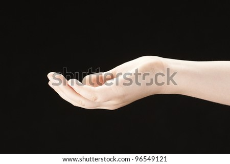 Girls hand with palm facing up - on black background