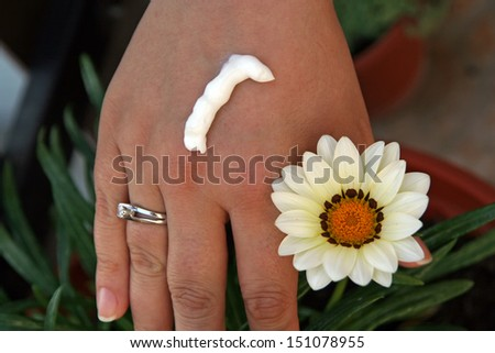 Girls hand with soft skin creme and a flower. - stock photo