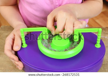 Girls hands collects shallow color beads - stock photo