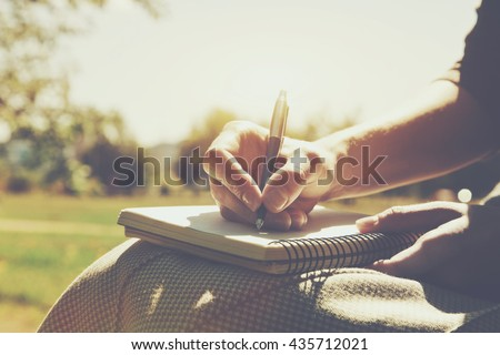 girls hands with pen writing on notebook in park - stock photo
