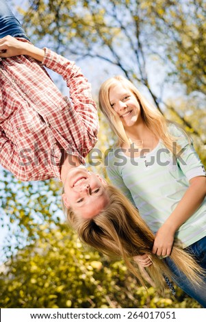 Girls having fun in park hanging upside down on green copy space background - stock photo