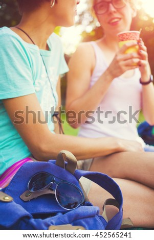 Girls having fun in the Park and drink coffee.