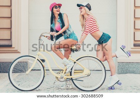 Girls having fun. Side view of happy young woman riding on bicycle while her female friend skating behind her - stock photo