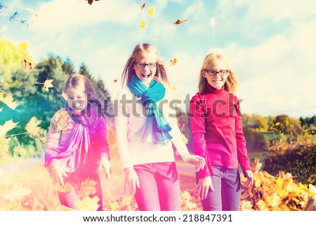 Girls having fun throwing fall or autumn leaves in park - filtered - stock photo