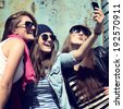 Girls having fun together outdoors and making photo with smart phone, lifestyle, toned - stock photo