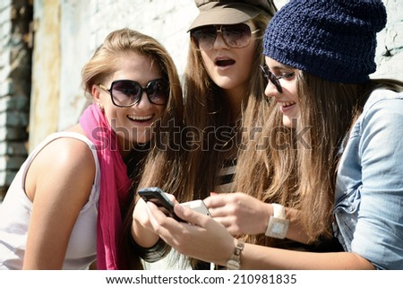 Girls having fun together outdoors using smart phone, lifestyle. Instagram effect. - stock photo