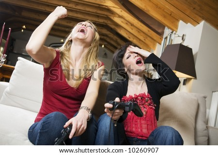 girls having fun with a new videogame - stock photo