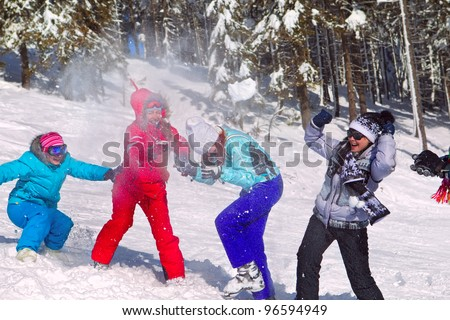 Girls having snowball fight in snow in winter background - stock photo