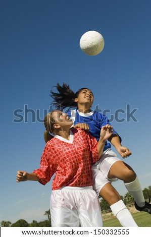 Girls heading soccer ball during match against blue sky - stock photo
