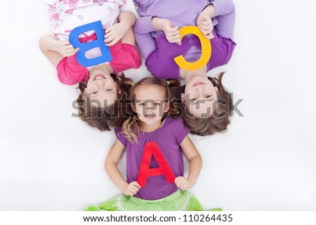 Girls holding A B C letters - laying on the floor
