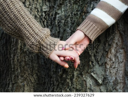 Girls holding hands against tree bark in autumn. - stock photo