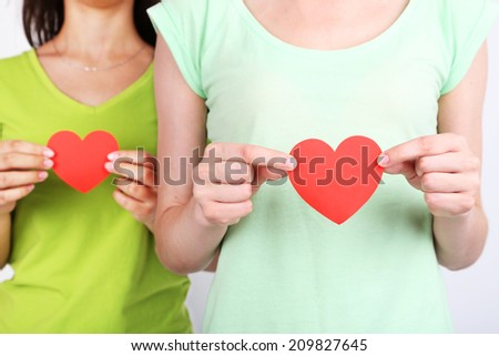 Girls holding red hearts  - stock photo