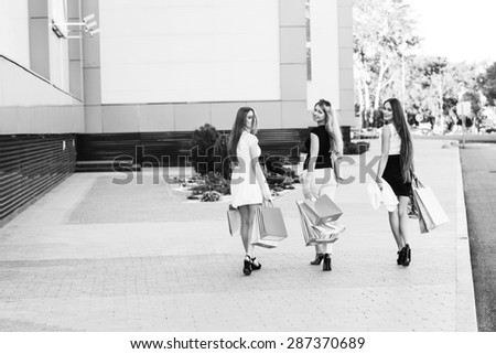 Girls holding shopping bags and walk around the shops. Smiling girlfriends having fun together - stock photo