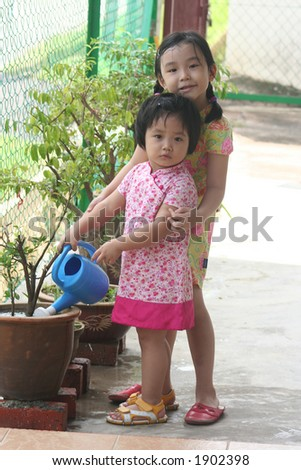 Girls holding watering-can watering plant