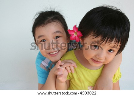 Girls hugging and showing funny face playing happily - stock photo