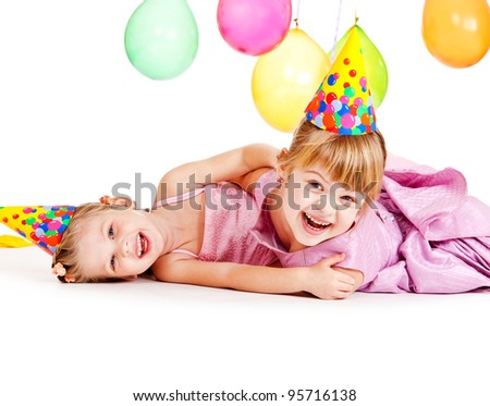 Girls in birthday hats, laughing - stock photo