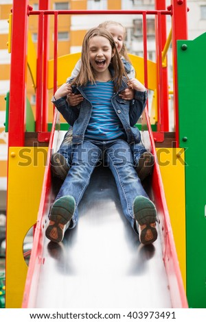 Girls in jeans suits slides down the hill on the playground - stock photo