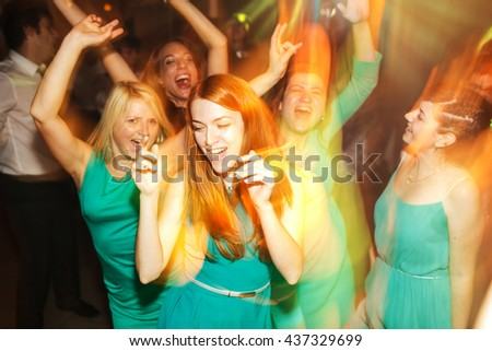 Girls in mint dresses have fun dancing in yellow lights