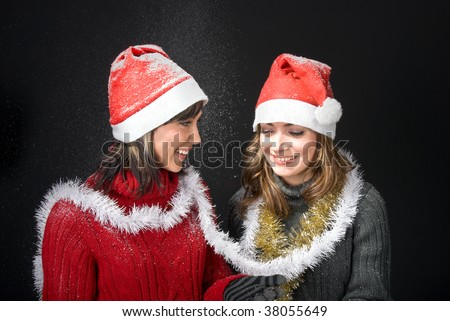 Girls in Santa's caps watching snowfall.