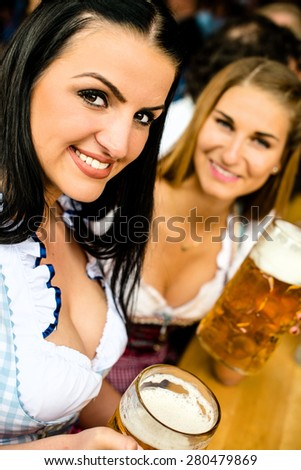 Girls in traditional Dirndl dress, one Russian touch but could also be Greek, one Caucasian are drinking beer and having fun at the Oktoberfest - stock photo