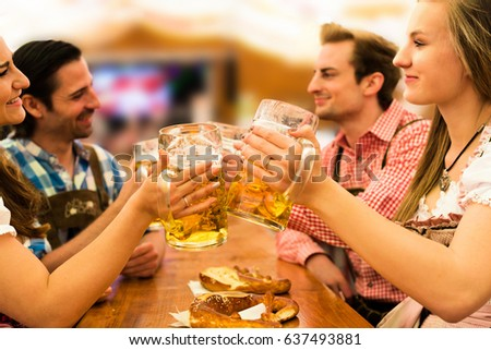 Girls in traditional Dirndl dresses are drinking beer and having fun with their friends at the Oktoberfest in Munich