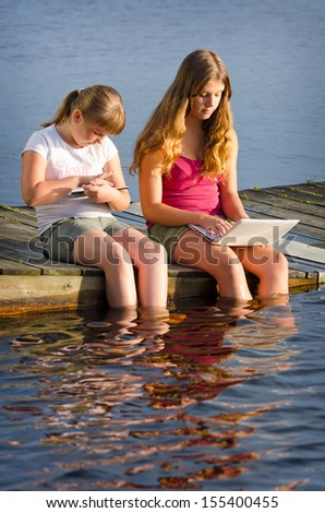Girls internet surfing in lake scenery - stock photo