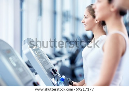 Girls involved in fitness on a treadmill - stock photo