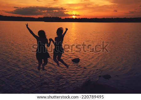 girls jump in the lake at sunset in summer - stock photo
