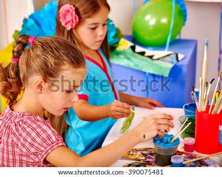 Girls keep brush painting on table in kindergarten . Painting learning. - stock photo