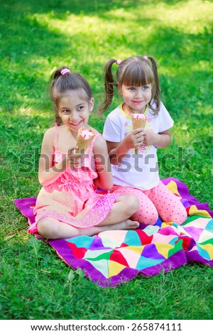 Girls kids sisters friends teasing eating ice cream, focus on younger girl's face - stock photo