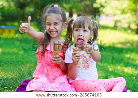 Girls kids sisters friends teasing showing off  tongues, sitting on grass, eating ice cream thumb up, focus on younger girl's face - stock photo