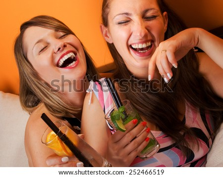 Girls laughing in dresses with cocktails