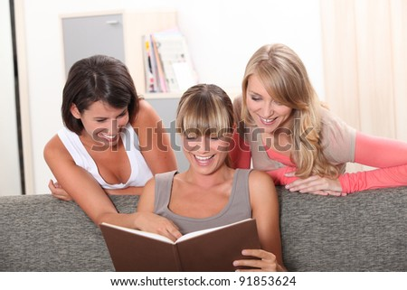 Girls laughing in front of a photo album