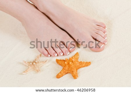 girls legs on beach sand - stock photo